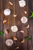 Взгляд сверху, плоское положение Шарик гвоздичного дерева чеснока и чеснока на коричневом деревянном столе Стоковые Фото