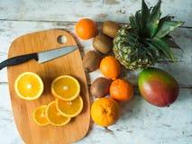 Взгляд сверху плодоовощей на таблице Апельсины, киви, манго, ананас Здоровая еда и концепция диеты на винтажных досках Стоковое Изображение RF
