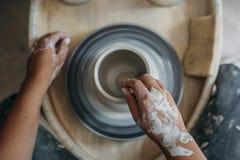 Взгляд сверху работ рук женщины гончара на колесе гончарни, гончаре делает новую керамическую продукцию стоковые изображения rf