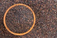Взгляд сверху риса ягоды риса с деревянными шаром и ложкой на деревянном Стоковое Фото