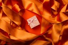 Взгляд сверху розовой малой подарочной коробки с лентой на оранжевом bac ленты Стоковые Изображения RF