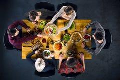 Взгляд сверху друзей на таблице с едой Стоковая Фотография