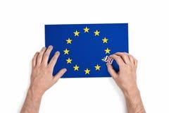 Взгляд сверху рук человека которое извлекает звезду от флага EC с Великобритани-введенным в моду ластиком изолировало на белой пр стоковые изображения