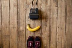 Взгляд сверху свежего зрелого банана, ботинок спорта и немедленной камеры Стоковая Фотография