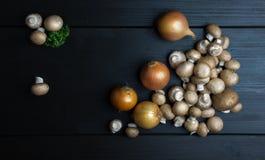 Взгляд сверху свежих грибов и лука с петрушкой на темном woode Стоковые Фото