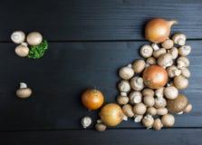 Взгляд сверху свежих грибов и лука с петрушкой на темном woode Стоковое фото RF