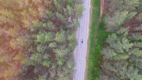 Взгляд сверху сняло на мотоциклисте ехать длинная узкая дорога 4K видеоматериал
