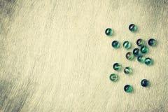 Взгляд сверху собрания сияющих мраморов на деревянной предпосылке. винтажное влияние. Стоковая Фотография