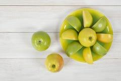 Взгляд сверху сочных желтых и зеленых яблок помещенных вокруг всего яблока на поддоннике Стоковые Фото