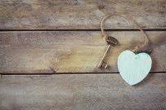 Взгляд сверху старого винтажного ключа с деревянным сердцем на деревянной предпосылке Стоковая Фотография RF