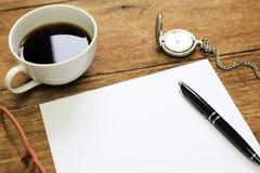 Взгляд сверху таблицы офиса с чашкой ручки чистого листа бумаги тетради Стоковое Изображение RF