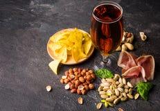 Взгляд сверху традиционных закусок и темного пива на серой предпосылке Арахисы, фисташки, мясо с стеклом пива холодно стоковое фото rf