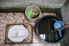 Взгляд сверху туалета традиционной и основной сельской местности тайского с тазом и ведром Стоковые Фото