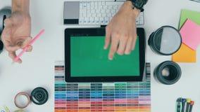 Взгляд сверху Укомплектуйте личным составом работу на зеленой таблетке экрана в студии дизайна предпосылка творческая акции видеоматериалы