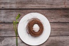 Взгляд сверху украшенного пасхального яйца в гнезде на заводе плиты и весны на деревянном столе, Стоковое фото RF
