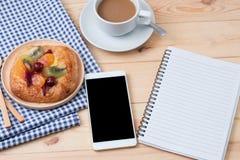 Взгляд сверху умного телефона с тетрадью и чашкой coffe искусства latte Стоковое фото RF