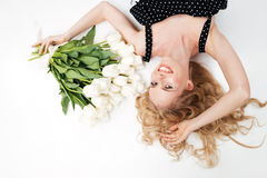 Взгляд сверху усмехаясь женщины лежа на поле с цветками Стоковое Фото