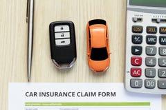 Взгляд сверху формы заявки страхования автомобилей с ключом автомобиля и автомобиль забавляются дальше Стоковое Фото