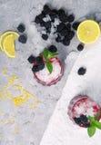 Взгляд сверху холодных напитков с мятой и ягодами Съемки ягоды на предпосылке льда Здоровые ежевики и отрезанные лимоны Стоковое Фото