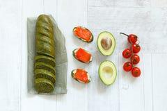 Взгляд сверху хлеба с шпинатом, семгами, авокадоом и томатами Стоковая Фотография RF