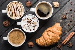 Взгляд сверху чашек кофе, кофейных зерен, круассана и специй Стоковое Изображение RF