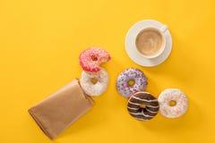 Взгляд сверху чашки кофе и нескольких donuts разбросало на желтую поверхность Стоковые Фото