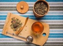 Взгляд сверху чашки чаю с кучей сухих трав на деревянном de Стоковые Фото