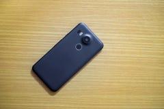 Взгляд сверху черного умного телефона на деревянном столе Стоковые Фото