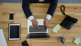 Взгляд сверху человека работая на компьтер-книжке и таблетке и умный телефон с пробелом касания зеленеют экран на таблице Стоковые Фото