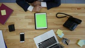 Взгляд сверху человека работая на компьтер-книжке и таблетке и умный телефон с пробелом касания зеленеют экран на таблице Стоковые Фотографии RF