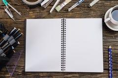 Взгляд сверху чистого листа бумаги и школьные принадлежности на темной древесине Стоковые Фото