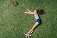 Взгляд сверху шарика рэгби маленькой sportive девушки заразительного на траве, стоковые фото