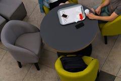 Взгляд сверху людей сидя на таблице в кафе Кафе самообслуживания Стоковая Фотография