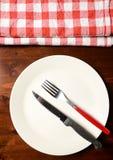 Взгляд сверху checkered салфетки на деревянном столе с плитой и cutl Стоковое Фото