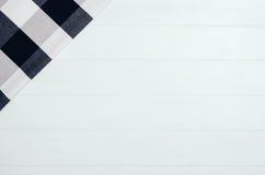 Взгляд сверху checkered салфетки ткани на белом деревянном столе Стоковое фото RF