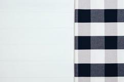 Взгляд сверху checkered салфетки ткани на белом деревянном столе Стоковое Фото