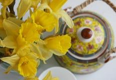 Взгляд сверху daffodils, чайника и чашки Стоковая Фотография