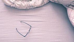 Взгляд сверху eyeglasses и кровати Стоковое Фото