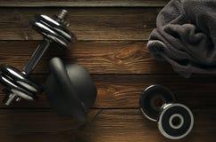 Взгляд сверху kettlebell черного листового железа, гантели и серого полотенца на wo Стоковые Изображения