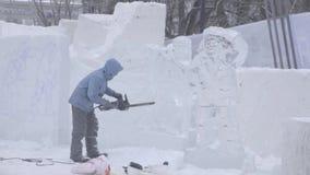 Взгляд скульптора высекая лед движение Отрежьте лед с цепной пилой Отрежьте и сделайте ледяную скульптуру Прерывать лед с осью акции видеоматериалы