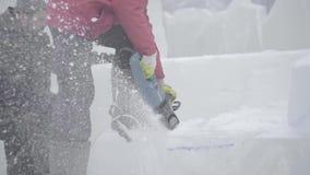 Взгляд скульптора высекая лед движение Отрежьте лед с цепной пилой Отрежьте и сделайте ледяную скульптуру Прерывать лед с осью видеоматериал