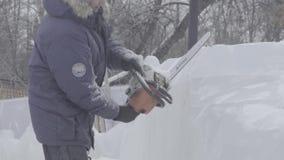 Взгляд скульптора высекая лед движение Отрежьте лед с цепной пилой Отрежьте и сделайте ледяную скульптуру Прерывать лед с осью сток-видео