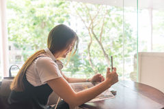 Взгляд со стороны азиатской девушки нося наушники, принимая selfie Стоковые Изображения