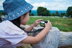Взгляд со стороны азиатской девушки ослабляя outdoors во времени дня, trave Стоковое Изображение RF