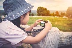 Взгляд со стороны азиатской девушки ослабляя outdoors во времени дня, trave Стоковая Фотография RF