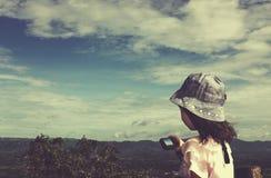 Взгляд со стороны азиатской девушки ослабляя outdoors в дневном времени, перемещении Стоковые Изображения RF
