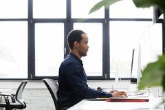 Взгляд со стороны африканского бизнесмена работая на компьютере Стоковое Фото