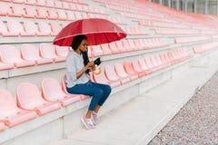 Взгляд со стороны афро-американской девушки беседуя через мобильный телефон пока сидящ под зонтиком на стадионе Стоковые Изображения RF
