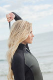 Взгляд со стороны белокурого в мокрой одежде стоя на пляже Стоковые Изображения RF