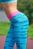 Взгляд со стороны бедра женщины пригонки над предпосылкой парка Стоковое фото RF